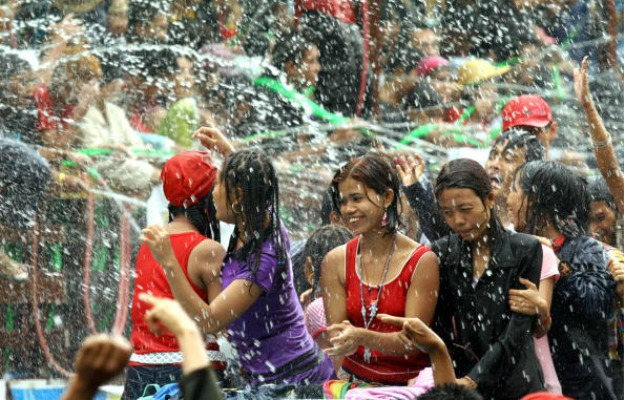 Locals get sprayed with water while celebrating Thingyan, Burma's New Year water festival, in Rangoon on 14 April 2011. (Reuters)