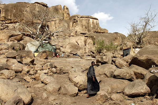A woman walks towards a cave shelter in Bram village in the Nuba Mountains in South Kordofan April 28, 2012. Fleeing aerial bombardment by the Sudanese air force thousands of people have abandoned their homes and made make-shift shelters between the rocks and boulders. (Goran Tomasevic / Reuters)